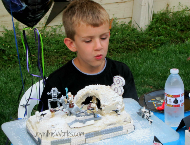 Birthday boy blowing out the candles on his Lego Star Wars Hoth Cake.