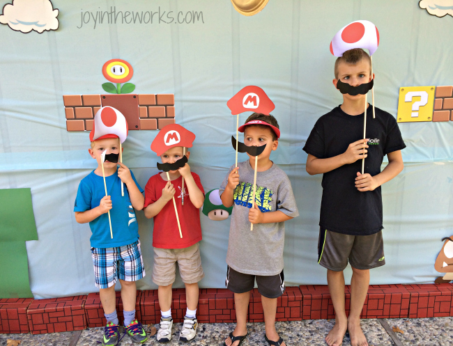 The boys using the photo props for the Super Mario backdrop