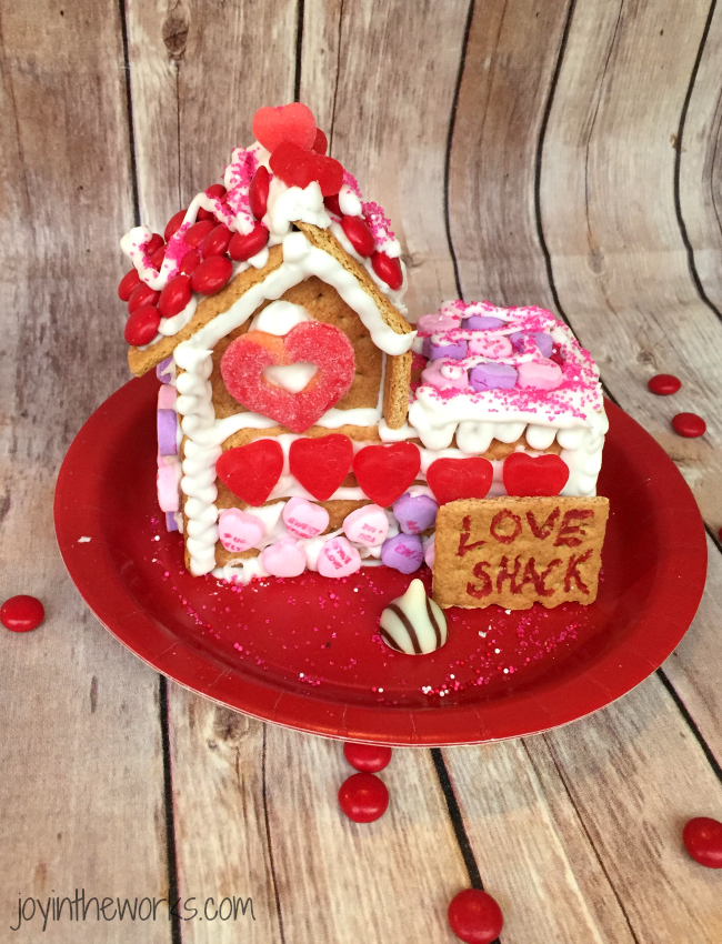 Gingerbread houses aren't just for Christmas! Why not take advantage of all the Valentine's Day candy and make a Valentine Candy House? So easy to make and so fun for the kids! A Valentine Gingerbread House (or Love Shack) would make a great Valentine's Day class party activity too!