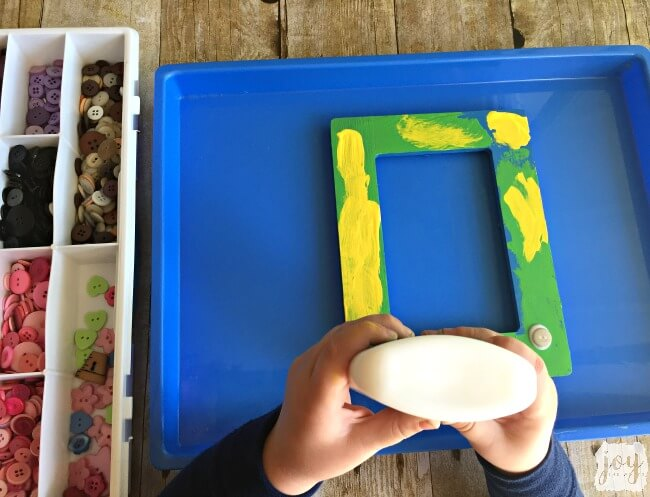 Looking for a kid made gift for mom, dad or a grandparent? A kid made button frame with a sweet picture of the child makes a great gift and is sure to please any relative!