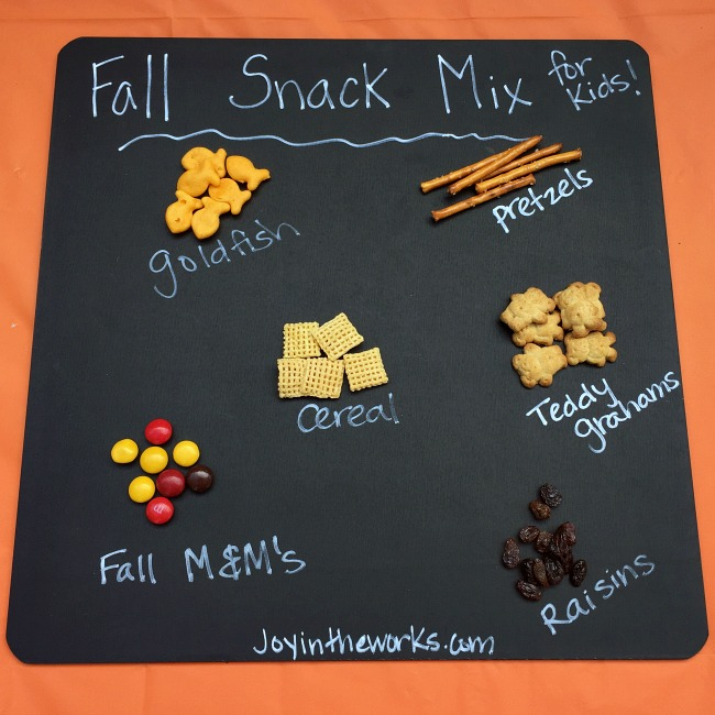 A (mostly) healthy Fall Snack Mix for kids with Goldfish Crackers, pretzels, raisins, cereal, Teddy Grahams and a small sweet treat with Fall M&M's
