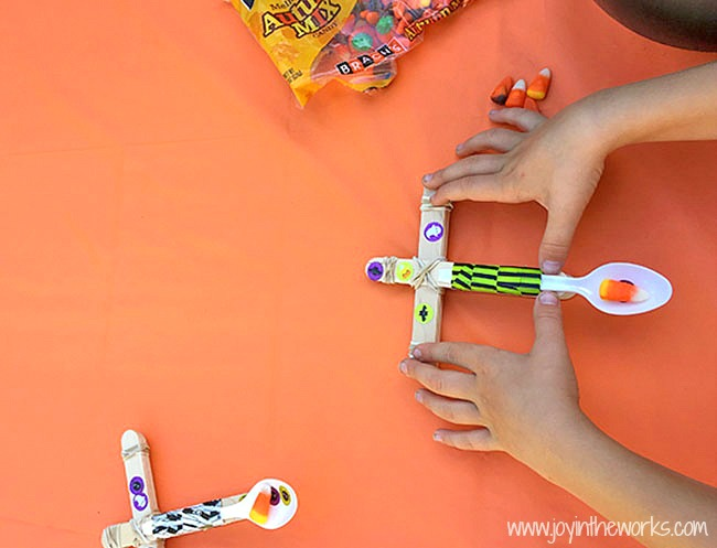 The perfect Halloween STEM activity is a Candy Corn Catapult! Even better? Try launching the candy corn, eyeballs and mini-pumpkins into cauldron targets!