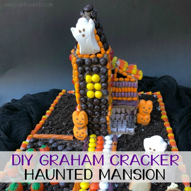 Forget the store bought Halloween Gingerbread House! Make a DIY Graham Cracker Haunted Mansion covered with candy instead! Step-by-step instructions available for how to make your own Halloween Graham Cracker House! Makes the perfect family fun activity after all the pumpkins are carved! Or even better? Make one with all of your leftover Halloween Candy! #halloween #halloweencandy #leftoverhalloweencandy #gingerbreadhouse #candyhouse #grahamcrackerhouse #hauntedhouse #hauntedmansion #halloweengingerbreadhouse #halloweengrahamcrackerhouse #diygingerbreadhouse #grahamcrackerhauntedmansion #gingerbreadhauntedmansion #familyfun #fallfamilyfun #fall